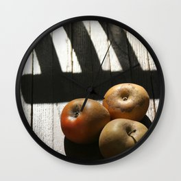 Three apples on a chair Wall Clock