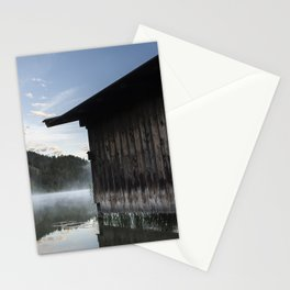 Boathouse with lifesaver at the lake. Amazing shot of a wooden house in the Ferchensee lake in Bavaria, Germany, in front of a mountain belonging to the Alps. Scenic foggy morning scenery at sunrise. Stationery Cards