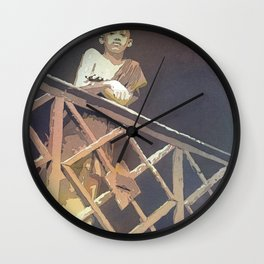 Buddhist monk standing by railing of Wat in the city of Phnom Penh- Cambodia. Wall Clock