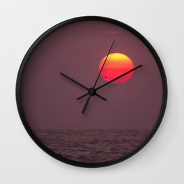 Bird flying into the Sunset Wall Clock