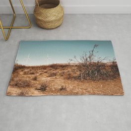 Desert and wind turbine with blue sky at Kern County California USA Rug