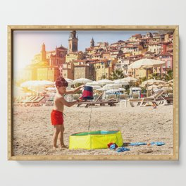 Young boy playing on a beach in French Riviera Serving Tray