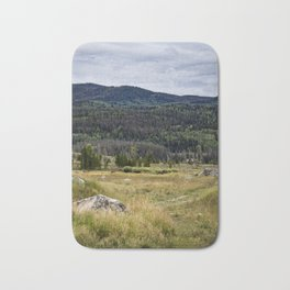 Grassy Meadow with Green Pine Trees and the Colorado Rocky Mountains in the Distance Bath Mat