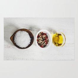 Salt, pepper and olive oil on a wooden board Rug