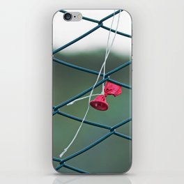 Deflated red balloon on fence net iPhone Skin