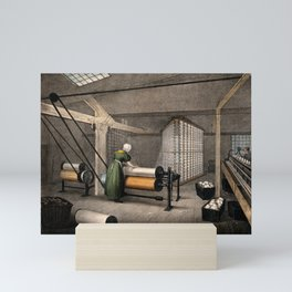 A woman is working at large rollers winding cotton onto reels. Coloured lithograph after Barfoot. Mini Art Print
