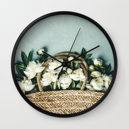 Beautiful peony flowers in straw bag over blue rustic background Wall Clock