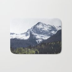 Winter and Spring - green trees and snowy mountains Bath Mat
