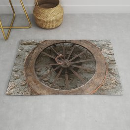 Wooden wheel hanging on a stone wall Rug
