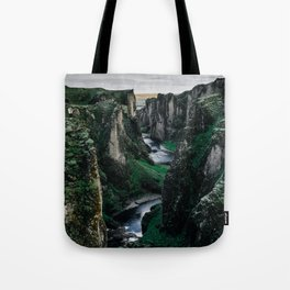 Fast flowing river making (wending) it's way between two massive rock formations Tote Bag