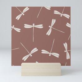 White Dragonflies against dark brown background.  Mini Art Print