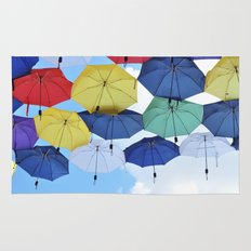many colorful hanged umbrella against blue sky Rug