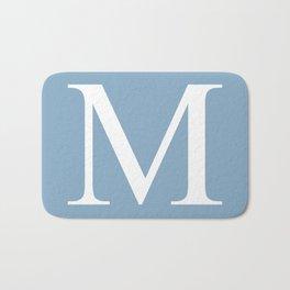 Letter M sign on placid blue background Bath Mat