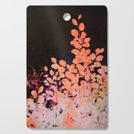 orange leaves against dark sky Cutting Board
