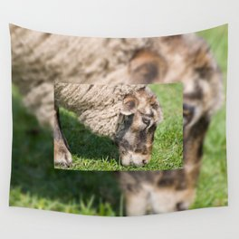 Single adult sheep eating grass Wall Tapestry