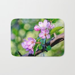 Bunch of pink crabapple flowers on a tree. Green background Bath Mat
