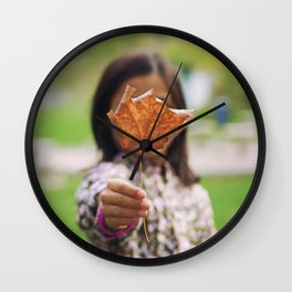Girl holding a dry leaf Wall Clock