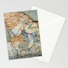 A urban city photograph of a destroyed wall and a graffiti of a boy carrying a Dinosaur Stationery Cards