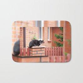 lonely stray black cat sitting Bath Mat
