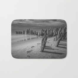 Footprints and Pilings on the Beach in Black and White at Kirk Park by Grand Haven Michigan Bath Mat