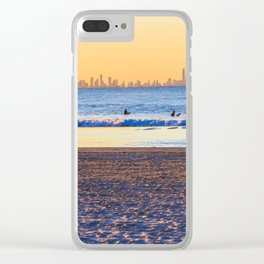 Surfer walks away from the sea on Coolangatta beach at sunset. Surfer's Paradise is in the backgroun Clear iPhone Case