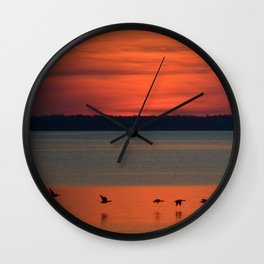 A flock of geese flying north across the calm evening waters of the bay Wall Clock