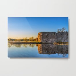 Ruins of old scandinavian castle or fort at sunset time at the lake Metal Print