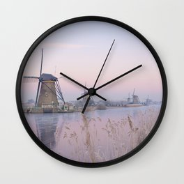 Pastel sunrise over windmills in winter in the Netherlands Wall Clock