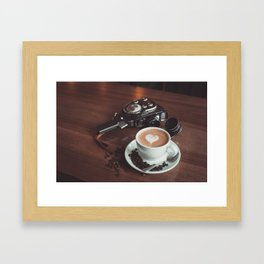 A cup of hot cappuccino placed on a table next to the old camera with lens and coffee beans Framed Art Print