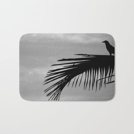 Bird silhouette with palm tree leaf in the Caribbean Bath Mat