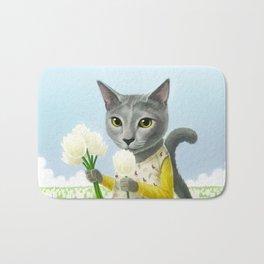 A cat sitting in the flower garden Bath Mat