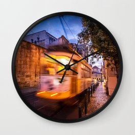 A tram transports tourists through the Alfama District in Lisbon, Portugal at dusk Wall Clock