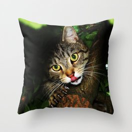 Cat licking nose hunting prey extending claws sitting on tree predator cat Throw Pillow