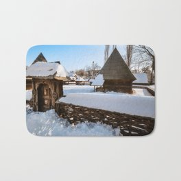 Traditional handcrafted gate and a rural Romanian homestead covered in snow Bath Mat