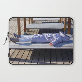 Young woman in winter jacket sunbathing on sun bed near sea. Winter holidays concept. Laptop Sleeve