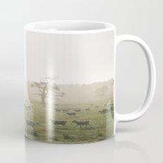 Sunrise burning through heavy fog over field of grazing sheep. Norfolk, UK. Mug