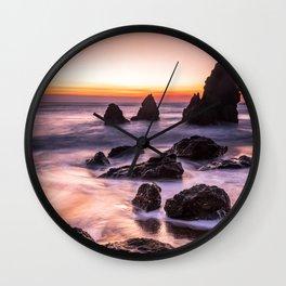 PHOTOGRAPHY OF BEACH NEAR BLACK ROCK FORMATION UNDER ORANGE SKY Wall Clock