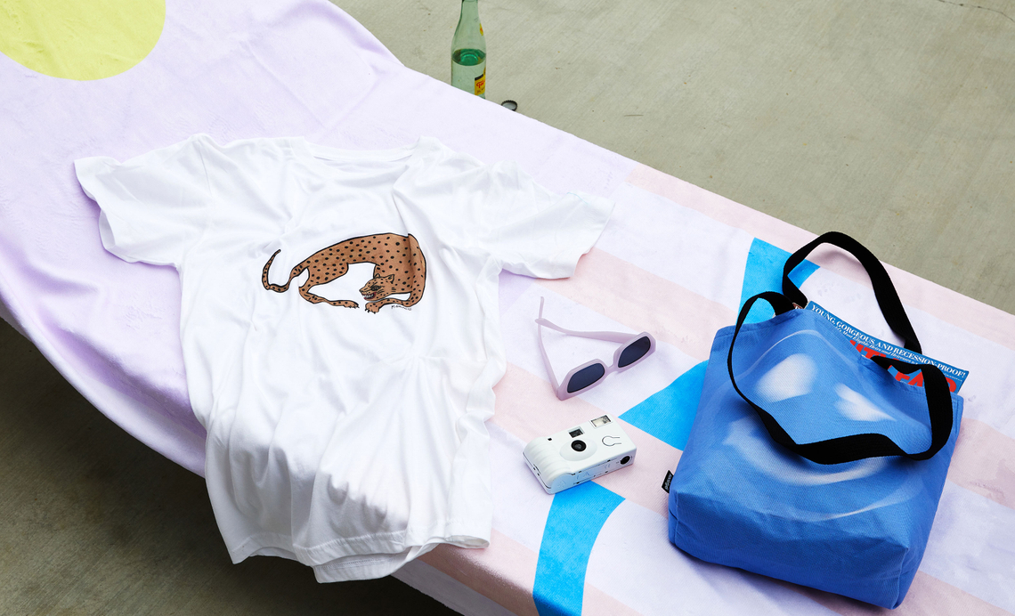pool chair with beach towel, t-shirt and tote bag on it