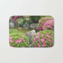 Japan stone garden with pink rhododendron flowers Bath Mat