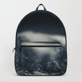Darkness and white clouds over the mountains Backpack