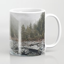 PERSON STANDING ON ROCK BESIDE BODY OF WATER BETWEEN GREEN TREES Coffee Mug