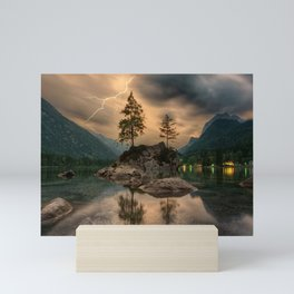 A scenic lake with Mountains & Lightning in the Distance. Mini Art Print