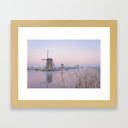 Pastel sunrise over windmills in winter in the Netherlands Framed Art Print