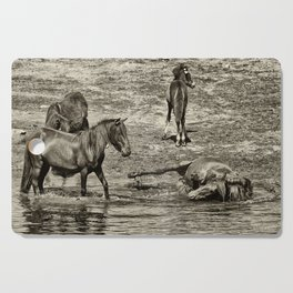Horses taking a bath and relaxing Cutting Board