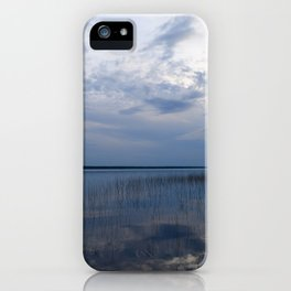 Sunlight in the cloudy blue sky is reflected in the clear spring water of the lake at sunset iPhone Case