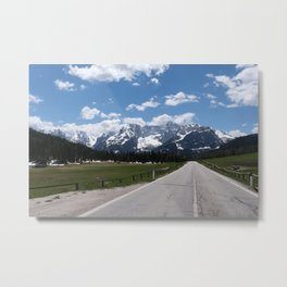 A shot on the move from the windshield of an electric car with italian snow-covered alps mountains in front of it. Sunny spring day. POV first person view shot on a mountain road. No people. Metal Print