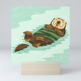 Cute sea otter floating in the kelp forest Mini Art Print