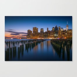 Sea side New York city in the evening with enlighten tall buildings, calm water and blue sky Canvas Print
