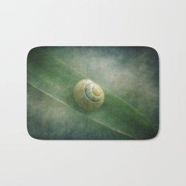 Shell in a sea of green Bath Mat