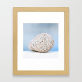 Granite pebble with blue water background Framed Art Print